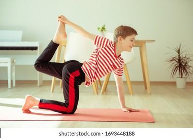 Teen boy doing yoga exercises at home due to coronavirus quarantine