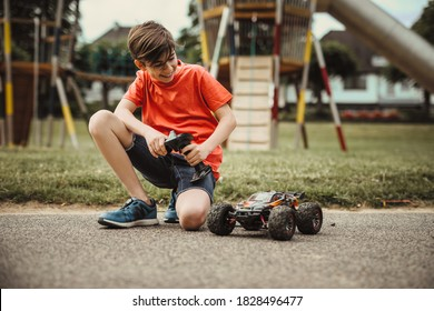 teen boy with electric remote control car toy play outdoor on sidewalk and have fun while enjoy his childhood