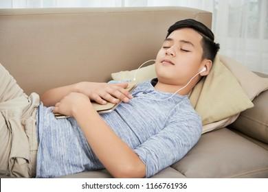 Teen boy fell asleep on sofa when watching videos on digital tablet