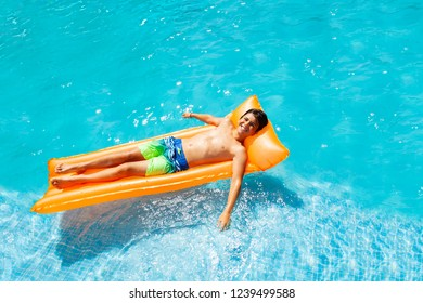 Teen boy floating on air mattress in swimming pool