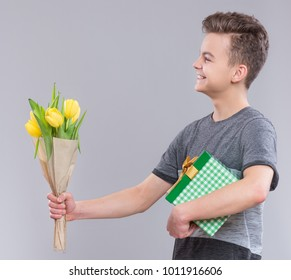 Teen boy with gift box and bunch of flowers on gray background. Smiling child with bouquet of tulips as a gift. Happy mothers or Valentines day!