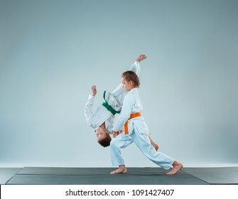 The teen boy and girl fighting at Aikido training in martial arts school. Healthy lifestyle and sports concept. Teenagers in white kimono on white background. Children with concentrated faces
