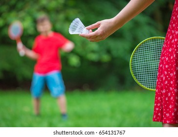Teen boy and girl playing badminton in meadow with forest in background. Children with badminton rackets. Friends have fun in park - with soft selective focus on female hand with shuttlecock.