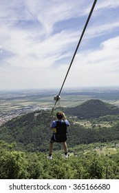 Teen boy going on a zip line adventure above a valley. Forest lay below and in the distance there are cultivated fields.