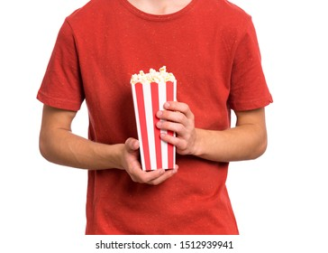 Teen boy hands with popcorn bucket, isolated white background. Child preparing to watch the film while holding popcorn. Close-up photo.