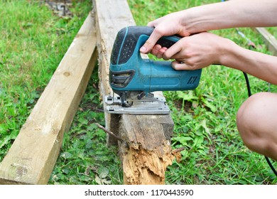 Teen boy hands using electric jig saw for cutting old wooden board outdoors on green grass in sunny summer day. Teenager practise to use carpenter tools and do it yourself concept.