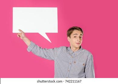 teen boy holding blank speech bubble isolated on pink