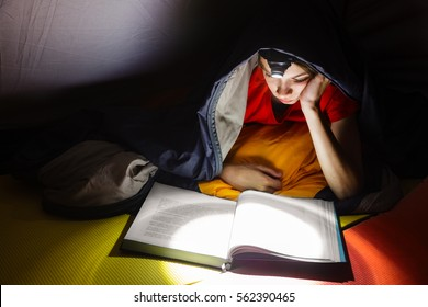Teen boy laying in a camping tent wrapped in a sleeping bag reading a book with flashlight on at night