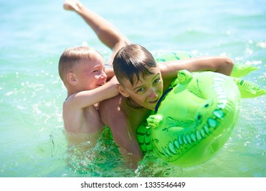 teen boy and little boy play in water on an inflatable crocodile toy
