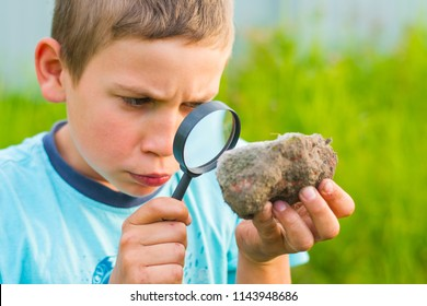 teen boy with a magnifying glass and examines the stone
