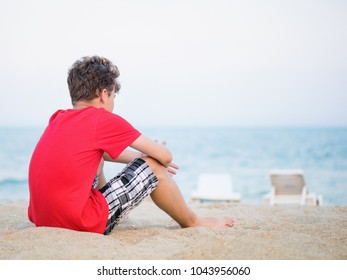 Teen boy on sand on beach - summer vacation, back view. Child looking away.