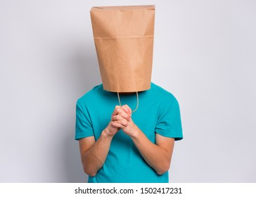Teen boy with paper bag over head praying. Teenager cover head with bag with hands folded in prayer hoping for better posing in studio. Child asking God for good luck, success or forgiveness.