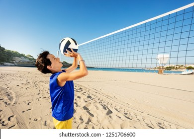 Teen boy passing ball playing beach volleyball