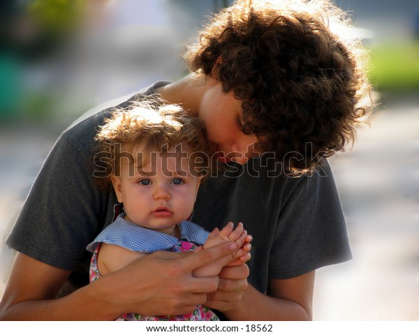 teen boy playing with a baby girl