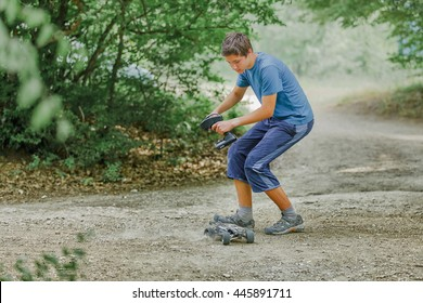 Teen boy with radio control car in green forest