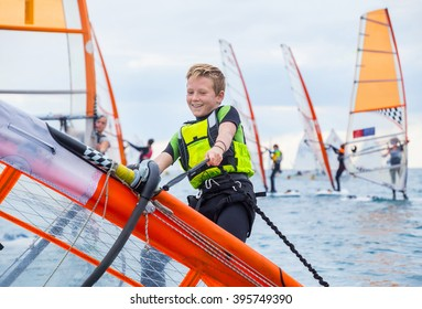 Teen boy raises windsurfing sail in the sea