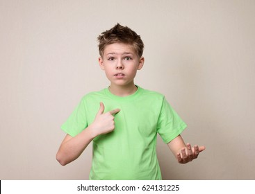 Teen boy rejecting the responsibility denying mistake with not me or who me? gesture.