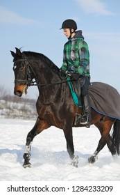 Teen boy riding horse in winter snow field