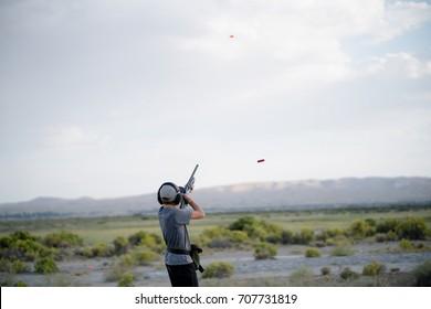 Teen boy shooting skeet in desert