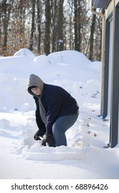 A teen boy shovels snow from in front of a house.
