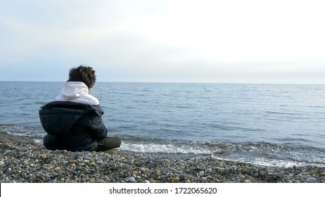 teen boy sitting alone on the beach in cold weather and looking out to sea.