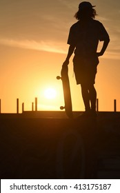 Teen boy with skateboard on skate park ramp at summer sunset, includes copy space and clipping path.