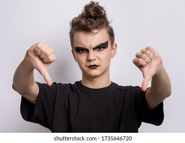 Teen boy with spooking make-up giving thumb down gesture looking with negative expression and disapproval. Teenager in style of punk goth dressed in black doing bad signal. Child on grey background.