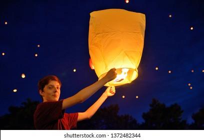 Teen boy in summer night with paper lantern