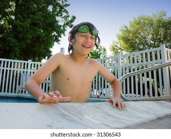 Teen boy with swimming goggles having fun at the pool.