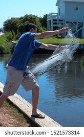 Teen boy throwing a casting net at the waters edge