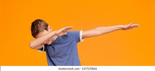 Teen boy throwing dab move, orange panorama background
