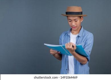 Teen boy wearing a blue shirt holding a book on a gray background.
