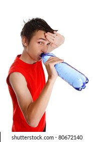 Teen boy wiping his brow and drinking water from a bottle.