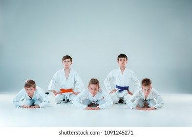 The teen boys and girl fighting at Aikido training in martial arts school. Healthy lifestyle and sports concept. Teenagers in white kimono on white background. Children with concentrated faces posing