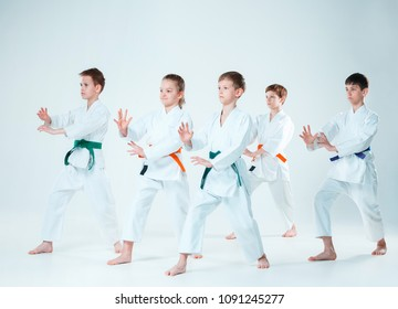 The teen boys and girl fighting at Aikido training in martial arts school. Healthy lifestyle and sports concept. Teenagers in white kimono on white background. Children with concentrated faces