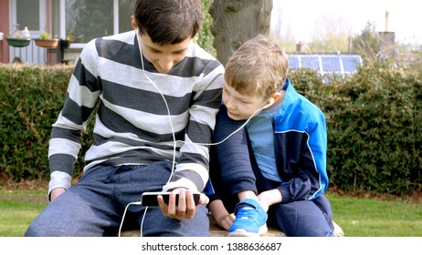 teen boys with smart phone listening or talking in british park on bench. teenager and social media concept