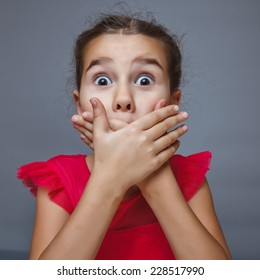 Teen brunette girl covering her mouth with her hands, experiencing a fright surprise bulging eyes portrait over gray background