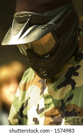 A teen in camouflage and mask ready for paintball.