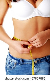 Teen caucasian girl measuring her stomach with yellow measuring tape, over white background.