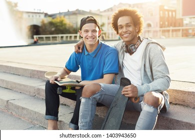 Teen diverse friends sitting outdoors with skateboards, ready for evening riding in urban skatepark, empty space