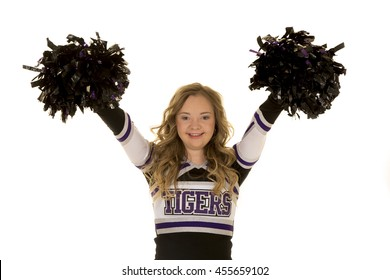 A teen with down syndrome in her cheerleader uniform smiling and posing.