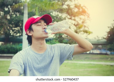 Teen drinking water after exercise.Thirsty.