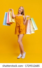 Teen Fashion. Pretty Young Girl In Jumpsuit With Lots Of Bright Shopping Bags Over Yellow Background, Empty Space