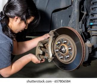 Teen female installs new disk breaks on a pickup