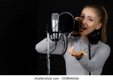 Teen female singer woking in voice studio with intention and happiness, she wears headphones singing go microphone with pop-up filter. Taken with dark light tone.