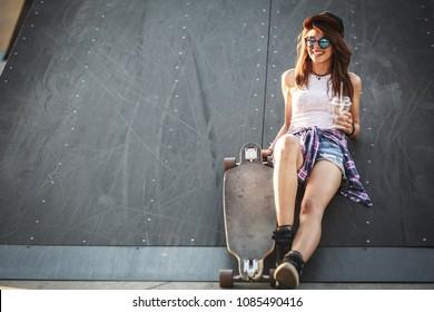 Teen female skater sitting on ramp at the skate park .