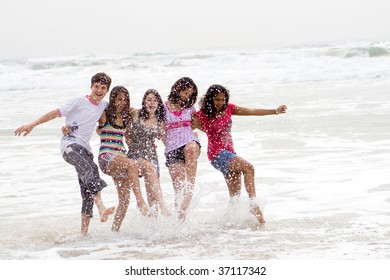 teen friends playing in sea water