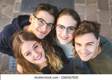 Teen friends portrait sitting together on a wall in the city. Close view  of two girls and two boys sitting together and embracing. Friendship and lifestyle concepts