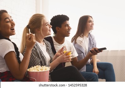 Teen friends watching tv, enjoying their day off and eating popcorn