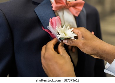 Teen gets help pinning his boutonniere to his suit lapel.